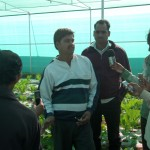 Community radio reporters interviewing a local agricultural research scientist