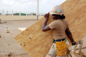 Female construction worker carrying a piece of wood on the work site.