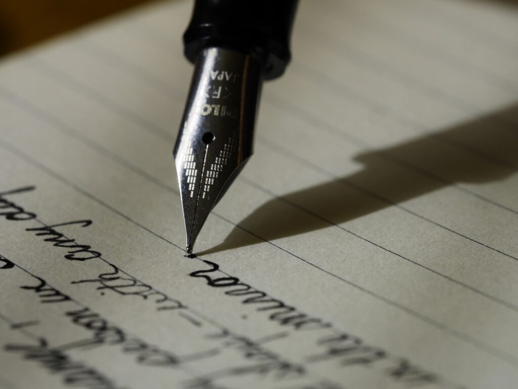 A fountain pen writing cursive on lined paper.